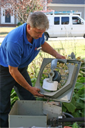 One of our certified air conditioning service men repairing an outdoor ac unit